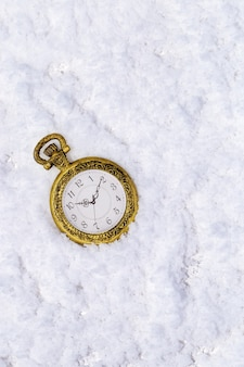 Tarjeta de felicitación de feliz navidad y feliz año nuevo con reloj de bolsillo dorado vintage sobre fondo de nieve con espacio de copia.