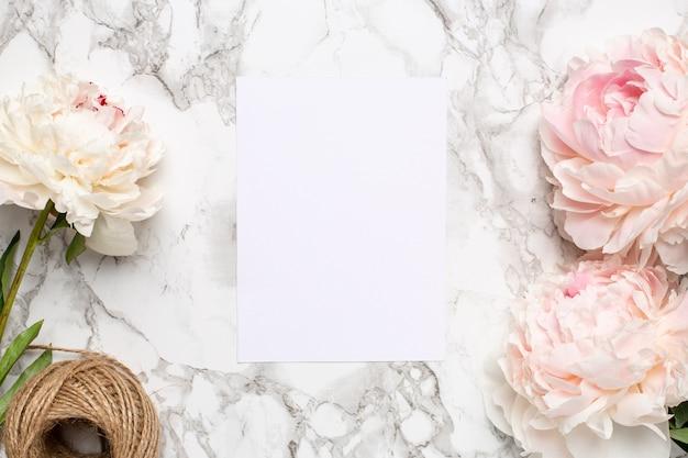Tarjeta de felicitación y flores de color rosa peonía en una superficie de mármol. artículo de vacaciones y verano.