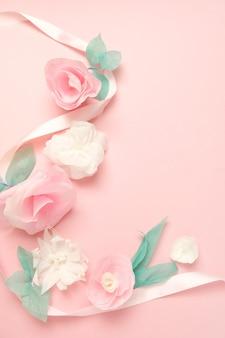 Tarjeta de felicitación con flores de papel rosa de fondo.