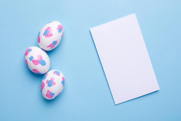 Tarjeta de felicitación y huevos de pascua con pinceladas de acuarela