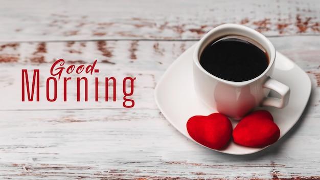 Tarjeta de felicitación con la inscripción buenos días. una taza de café con corazones rojos.