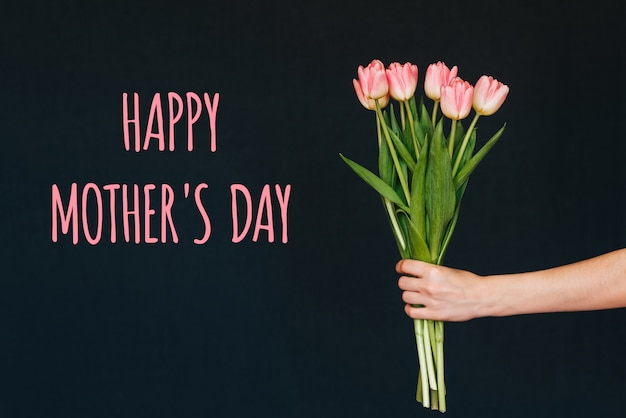 Tarjeta de felicitación con la inscripción feliz día de la madre. ramo de flores de tulipán rosa en mano de mujer