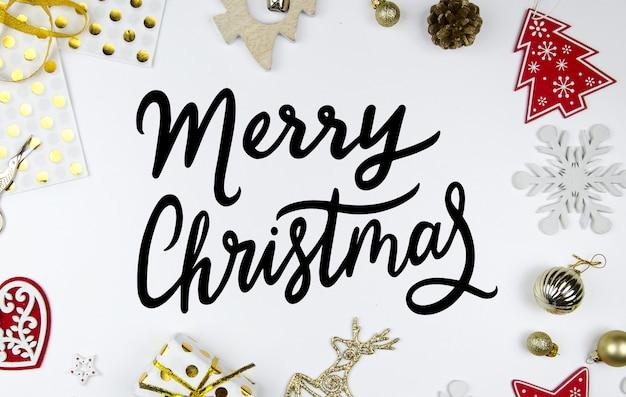 Tarjeta de felicitación de letras de mano de feliz navidad. escena de estilo con decoraciones navideñas