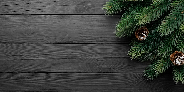 Tarjeta de felicitación de navidad con abeto y piñas sobre fondo negro de madera