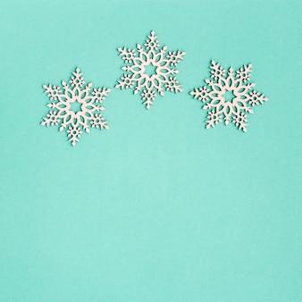 Tarjeta de felicitación de navidad con copos de nieve de madera sobre fondo de papel de menta con espacio de copia. decoración de año nuevo.