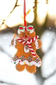 Tarjeta de felicitación de navidad con gingerbread man cookie toy colgando de una rama de árbol
