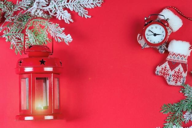 Tarjeta de felicitación de navidad con linterna roja, reloj rojo, ramas de nieve y mitones en rojo