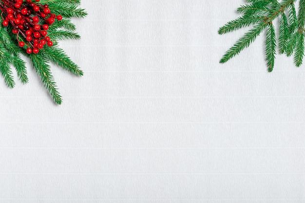 Tarjeta de felicitación de navidad. rama de agujas verdes y bayas de acebo rojo sobre papel corrugado blanco.