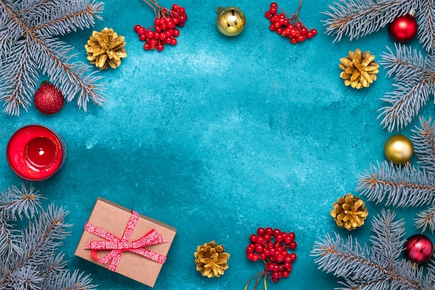 Tarjeta de felicitación de navidad con ramas de abeto azul y piñas doradas. racimos de bayas rojas de viburnum