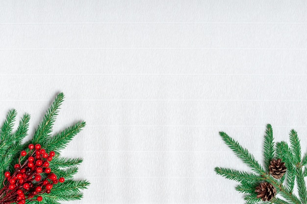 Tarjeta de felicitación de navidad. ramas de abeto y bayas de acebo sobre papel corrugado blanco.