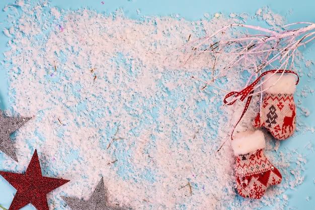 Tarjeta de felicitación de navidad con ramas de nieve y guantes en azul nieve