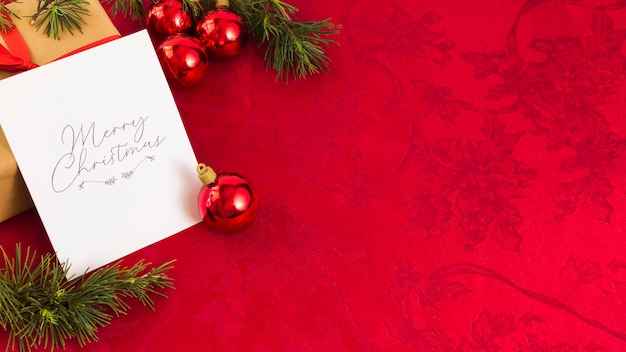 Tarjeta de felicitación navideña con adornos rojos.