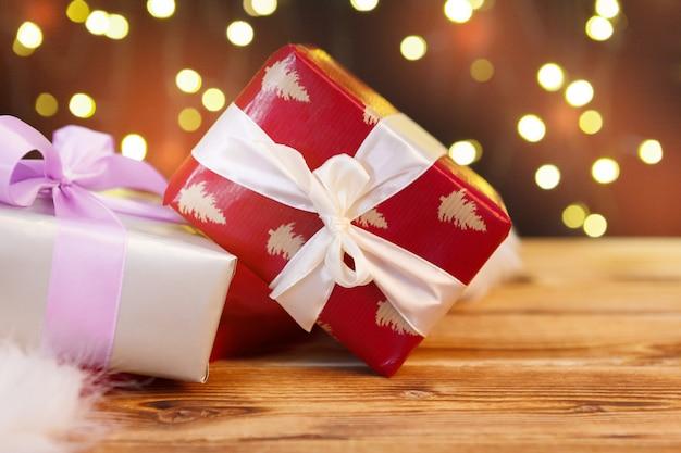 Tarjeta de felicitación navideña con cajas de regalo sobre fondo de luces borrosas