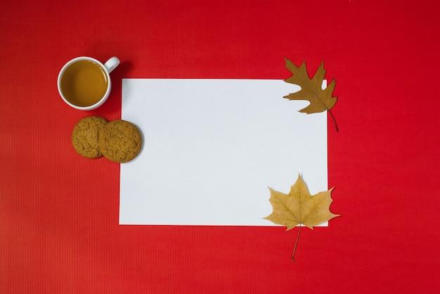 Tarjeta de felicitación de otoño maqueta blanca de una hoja de papel con decoración de follaje una taza de té