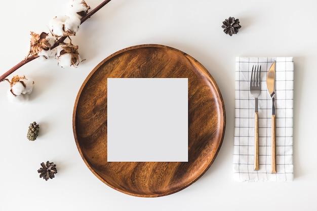 Tarjeta de felicitación de papel en blanco en plato de madera, cubiertos con servilleta a cuadros, flores de algodón