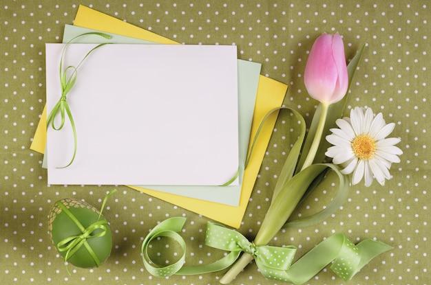 Tarjeta de felicitación de pascua con flores, huevo y cintas.