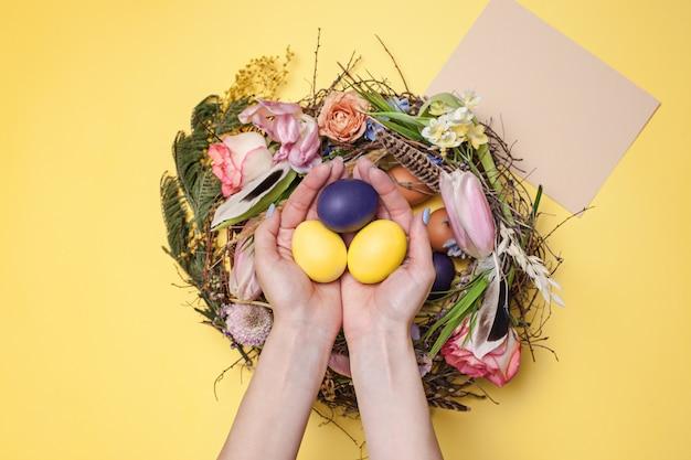Tarjeta de felicitación de pascua. huevos de pascua pintados en el nido