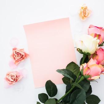 Tarjeta de felicitación con rosas y pétalos en blanco
