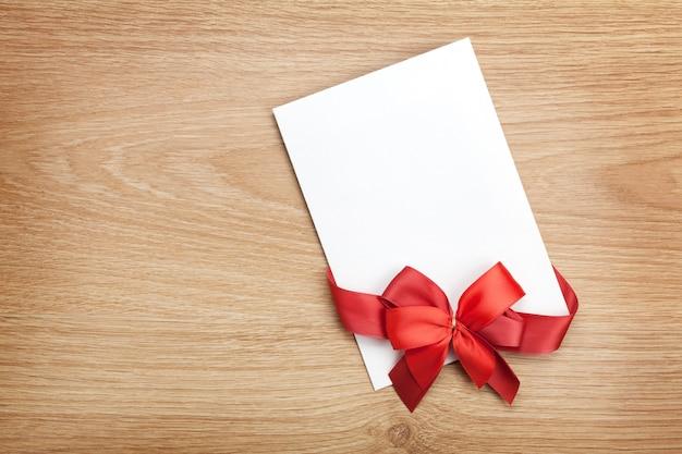 Tarjeta de felicitación de san valentín en blanco y cinta roja sobre fondo de madera con espacio de copia