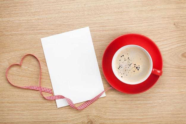 Tarjeta de felicitación de san valentín en blanco y taza de café roja sobre fondo de madera