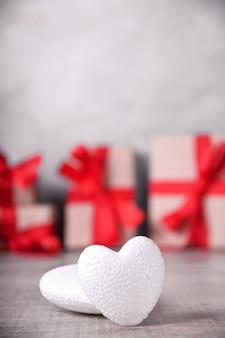 Tarjeta de felicitación de san valentín con corazones sobre fondo de madera y regalo. con espacio para tus saludos de texto