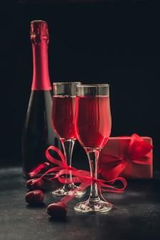 Tarjeta de felicitación de san valentín y cumpleaños con regalo y vino espumoso rojo sobre negro.