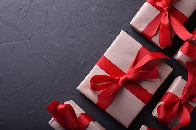 Tarjeta de felicitación de san valentín fondo símbolos de amor, decoración roja con cajas de regalos sobre fondo de piedra. vista superior con espacio de copia y texto.