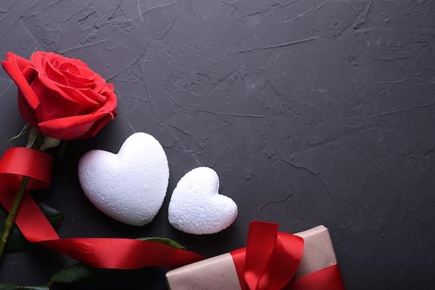 Tarjeta de felicitación de san valentín fondo símbolos de amor, decoración roja con corazón sobre fondo de piedra. vista superior con espacio de copia y texto.
