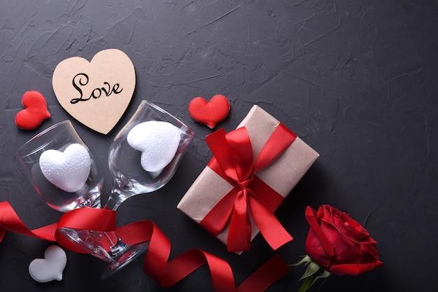 Tarjeta de felicitación de san valentín fondo símbolos de amor, decoración roja con gafas corazón rosas regalos en mesa de piedra. vista superior con espacio de copia y texto.