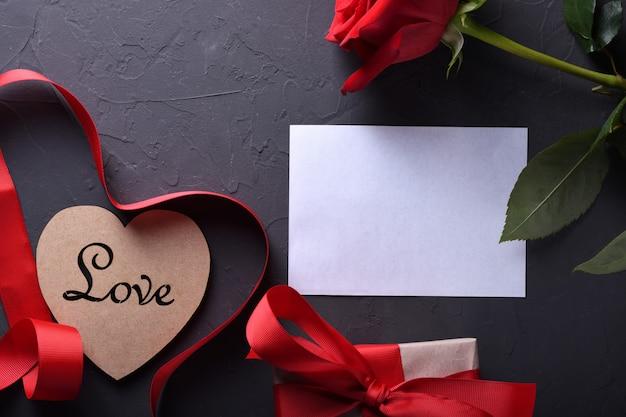 Tarjeta de felicitación de san valentín fondo símbolos de amor, decoración roja con gafas corazón rosas regalos sobre fondo de piedra. vista superior con espacio de copia y texto.