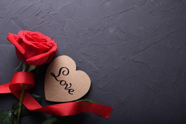 Tarjeta de felicitación de san valentín fondo símbolos de amor, decoración roja con rosas sobre fondo de piedra. vista superior con espacio de copia y texto.