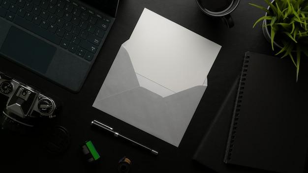 Tarjeta de felicitación con sobre gris en el oscuro escritorio de oficina con dispositivos digitales y suministros de oficina