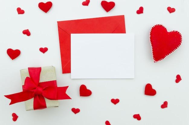 Tarjeta de felicitación con sobre rojo, caja de regalo y corazones. valetnines dia amor maqueta. lay flat