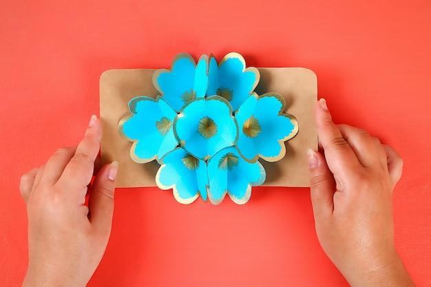 Tarjeta de felicitación tridimensional 3d de diy con las flores para el día de madres en un fondo coralino vivo.