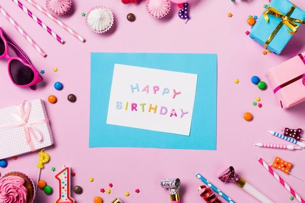 Tarjeta de feliz cumpleaños rodeada de artículos de cumpleaños sobre fondo rosa