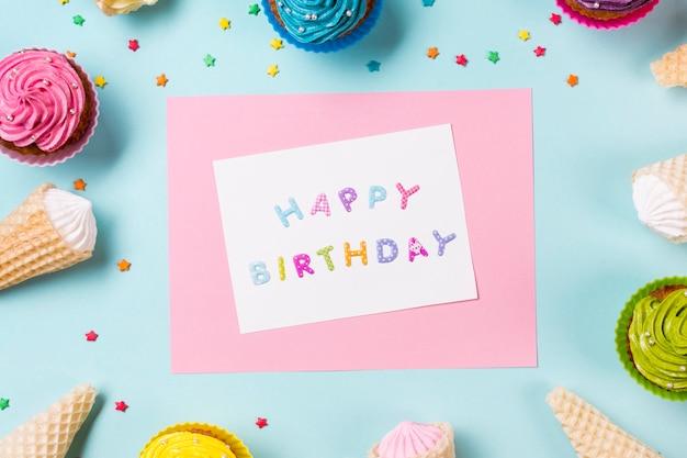 Tarjeta de feliz cumpleaños rodeada de muffins; cono de galleta y espolvoreado sobre fondo azul