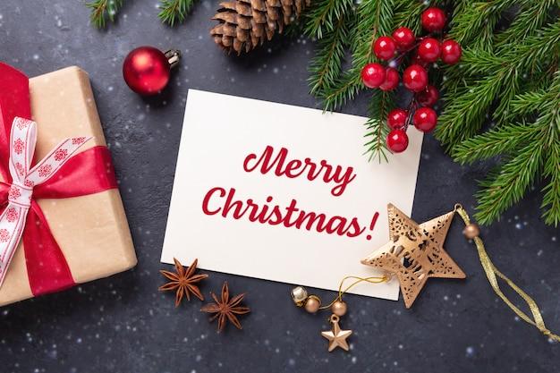 Tarjeta de feliz navidad con papel, caja de regalo y rama de abeto sobre fondo negro