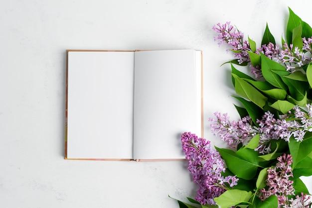 Tarjeta festiva de vacaciones de flores lilas frescas y cuaderno de papel sobre un fondo de mármol gris claro. vista superior.