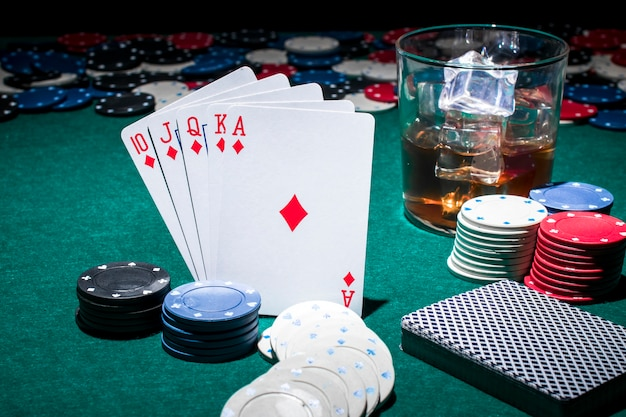 Tarjeta; fichas de casino y vaso de whisky en la mesa de póquer