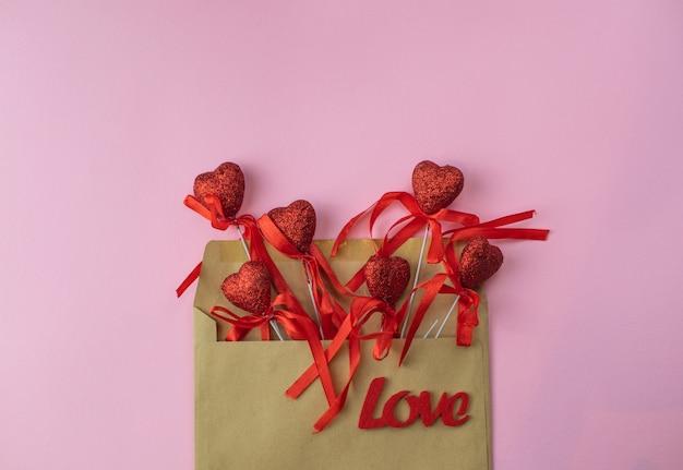 Tarjeta de fondo rosa romántico san valentín con sobre con corazones