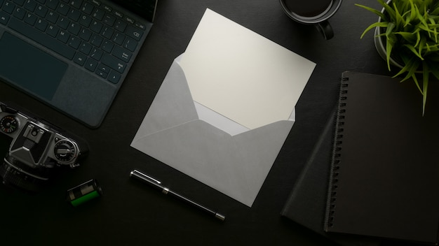 Tarjeta de invitación abierta con sobre gris en el escritorio de oficina moderno oscuro con suministros de oficina