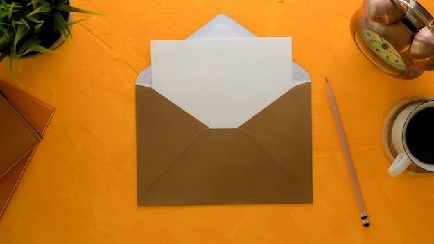 Tarjeta de invitación abierta con sobre marrón en mesa de trabajo creativa con libros de horarios y decoraciones