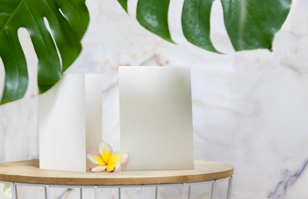 Tarjeta de invitación blanca y flor de plumeria en flor.