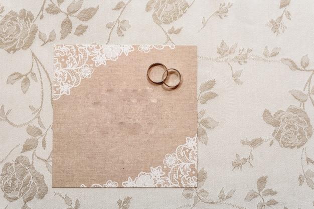 Tarjeta de invitación de boda con anillos, vacía con espacio para rellenar con texto.