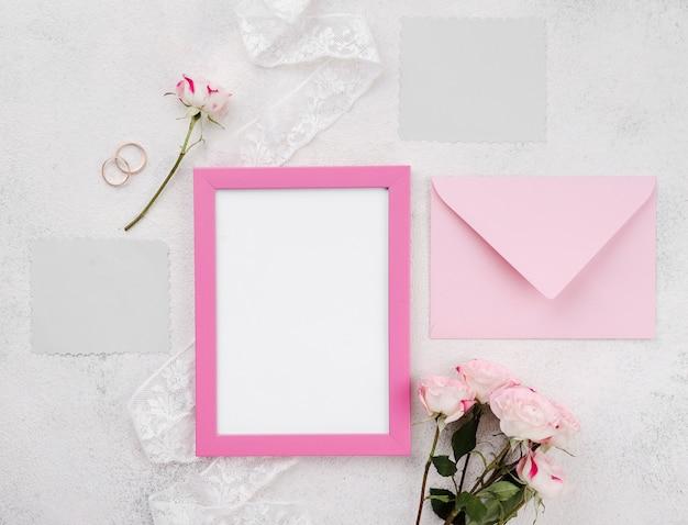 Tarjeta de invitación de boda con marco sobre la mesa
