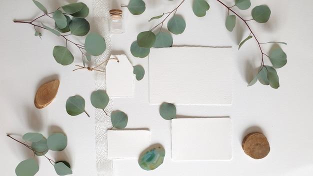 Tarjeta de invitación de felicitación de boda blanca en blanco, etiqueta, ágata, rama de hojas de eucalipto plateado, sobre fondo de mesa de papel con textura. plantilla moderna elegante vista superior plana