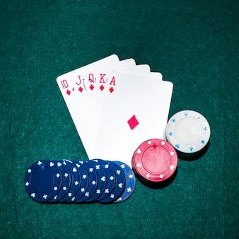 Tarjeta de juego royal flush y fichas de casino en la mesa de póquer