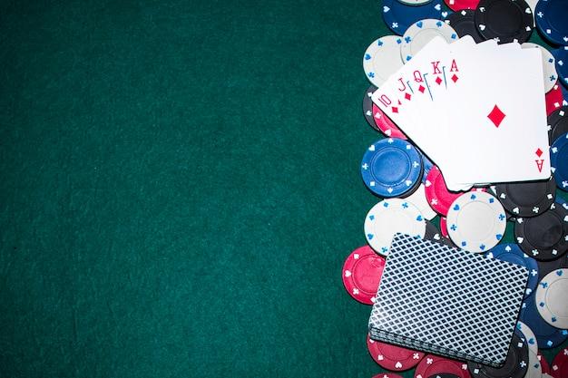Tarjeta de juego royal flush sobre las fichas de casino en la mesa de póquer verde