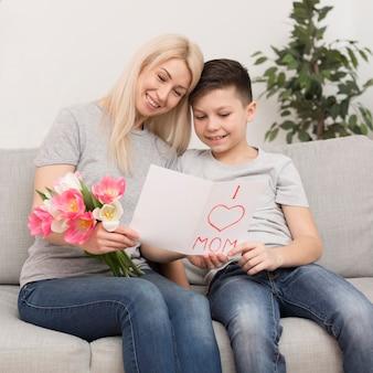 Tarjeta de lectura de niño y madre de ángulo bajo