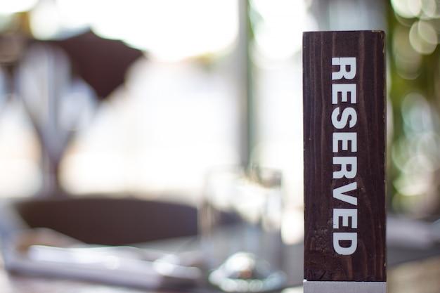 Tarjeta de madera reservada sobre fondo borroso reserva en restaurante - ocio y servicio c